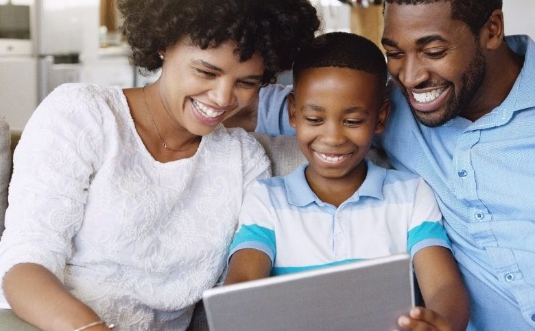 Family gathered around computer learning about financial wellness